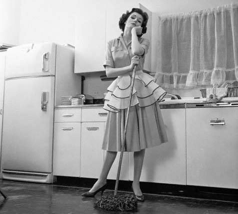 1950s Bored Woman Housewife Wearing Apron Leaning On Mop On Kitchen Floor